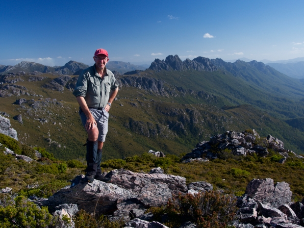 Graham stands on the summit of Innes High Rocky, the Spires behind