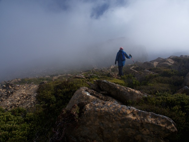 Graham leads off into the mist, Eldon Crag is faintly visible