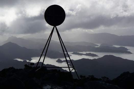 A black trig, white moon, silver sky, mountains in 50 shades of grey